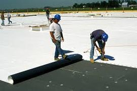 Employees working on a TPO roofing system
