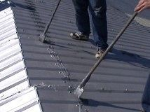 Employees installing a metal roof